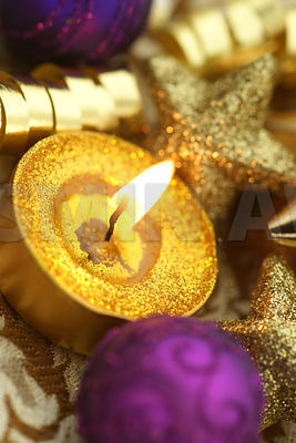 Holiday candle with gold and purple decoration Close up Studio shot