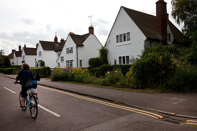 UK - Letchworth Garden City - A woman cycles her bicycle past  Arts and Crafts styled houses in Letchworth, the world's first Garden City designed by Ebenezer Howard to marry the best of urban and rural living.