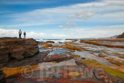 Colourful Rocks on the Coast with two People in the DIstance
