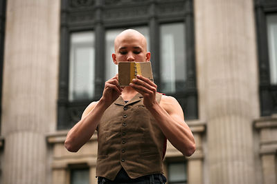 Circus Performer Reading Book in a Performance in Regent Street London