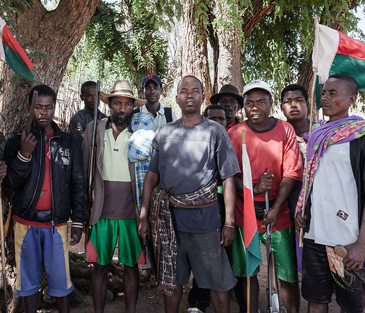 "BEHAHITSE COMMUNE - Members of the Betioky ""fokonolona"" (community) met in Behahitse village, Ampanihy district, southern Madagascar. They are subject to the authority of a ""Dina Be"" (reconciliation). I am informed that most of them are zebu thieves (Dahalo). They still come armed and protected with their amulets (ody gasy) ""because you never know"" they tell me. They visit the Behahitse fokonolona to claim their due: nine zebus must be reimbursed to the Betioky community because a Behahitse resident stole a bicycle there. But the fokonolona of Behahitse does not agree, he finds that it is too much and contrary to the rule that was established by the Dina Be. Normally the refund should be three zebus and not nine. The two parties meet under tamarind trees near the village market. A long ""kabary"" (discussion, speech) of one day will finally bring the two parties together. To seal this pact, a zebu will be killed and shared."