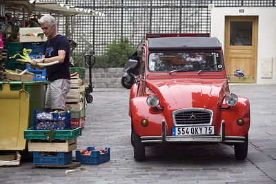 France - Paris - A man cleans vegetables behind a market stall next to a typically French car on the Rue Mouffetard.