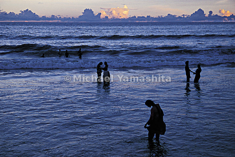 Couples enjoy a moment while standing in the shallow water of the Arabian Sea.