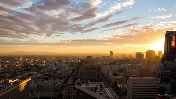 Bird's Eye: Brilliant Sunset With Low Level Stratus, Busy City Streets, & A Neon Skyline (Dolly)