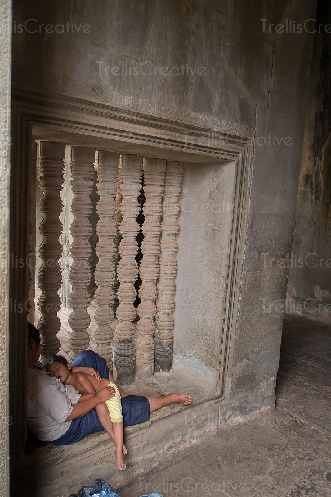 A woman sleeping with her son on window sill inside the temple at Angkor Wat