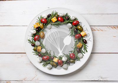 Rosemary wreath christmas appetizer with cheese and olives on plate on wooden background