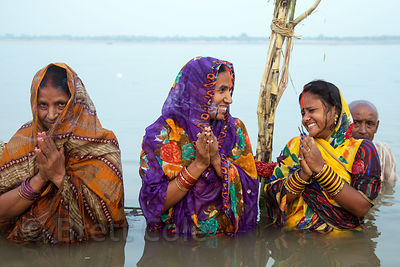 Ladies pray in the Ganges River during Chhath Puja, Varanasi, India. Chhath Puja is a devotion to the Sun God Surya in which people gather at sunset and then on the following sunrise and offer prayers.