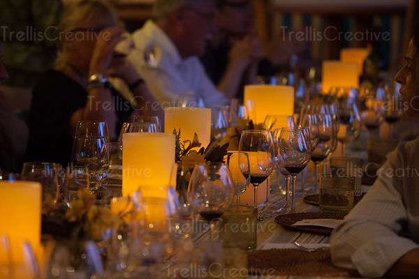 Warm and inviting candlelit dinner table with people drinking wine