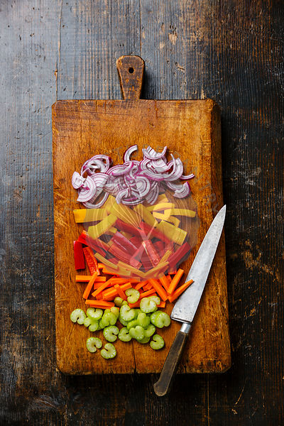 Sliced fresh vegetables for salad and table knife on cutting board on wooden background
