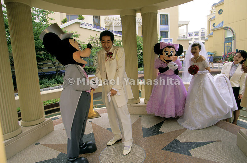 M-I-C-K-E-Y and his mate charm a beaming bride and her bashful groom, wed at Tokyo Disneyland. Japan's long post-war occupation by U.S. troops helped give rise to a deep affinity for American pop culture, which has made this Disney export the world's most visited theme park.