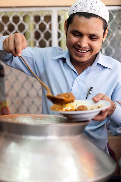 India - Delhi - A man serves Mutton Korma at the Al Jawahar Restaurant on Matia Mahal