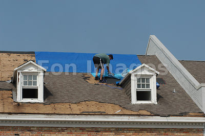 Workers repair roof in Biloxi, MS damaged by Hurricane Katrina