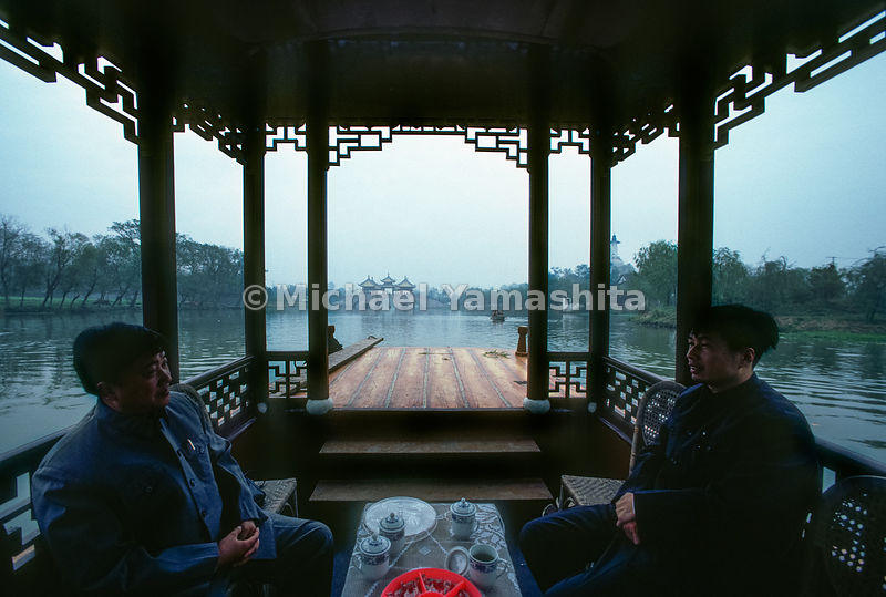 Two men enjoy tea on Slender West Lake, China.