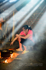 Young Hmong Woman Cooking Inside Hut in Rays of Sunlight