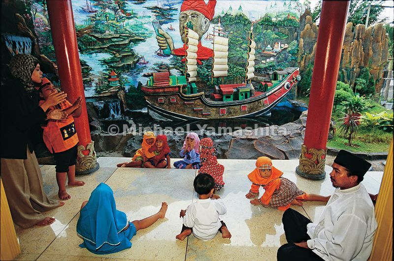 Children take their lessons in Koran school against a backdrop of one of Zheng He's (or Cheng Ho, as he is known here) treasure ships and mural dedicated to his exploits.
