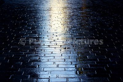 Closeup of Wet Brick Pavers in Mathew Street with a Strong Backlight Reflection