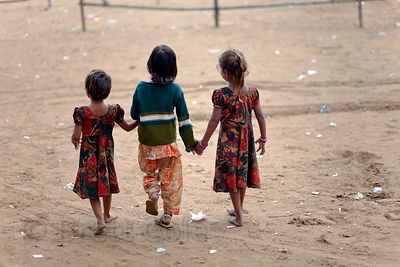 Three girls holding hands in Pushkar, Rajasthan, India