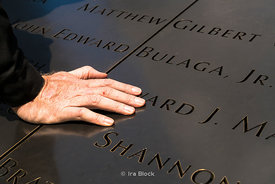 A hand on the names of the deceased at the 9/11 memorial North pool.