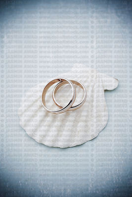Rose wedding rings on seashell Blue wood background with copy space for text