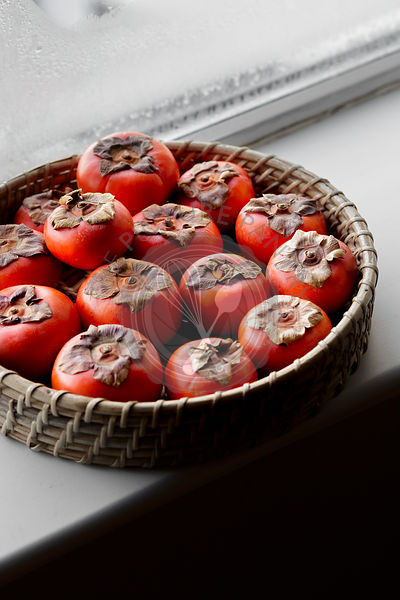Persimmons in a basket on a window ledge