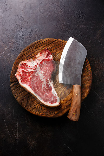 Raw Dry Aging Steak meat T-bone and Butcher cleaver on cutting board on dark background
