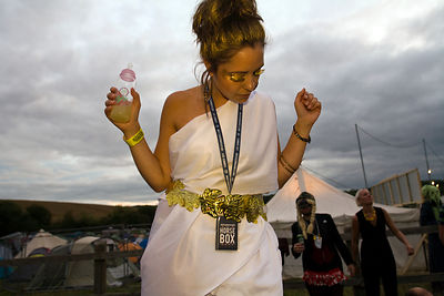 UK - Standon - A woman in costume dances in a field to a mobile sound system at the Standon Calling Festival