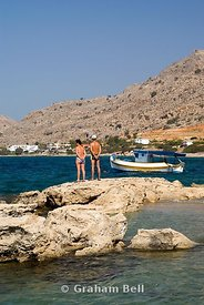 middle aged couple standing on rocks looking at view, pefkos, lindos, rhodes, dodecanese islands, Greece.