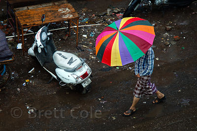 A man walks under a colorful umbrella during monsoon rains in Bandra East, Mumbai, India.