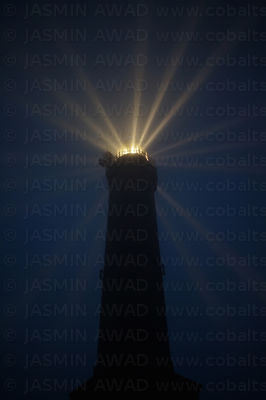 Old Lighthouse tower at night emitting radial light beams North Sea Coast Germany