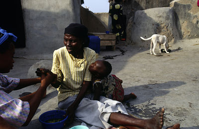 Ghana - Arigu - Asumpaheme, who is blind, rolls food in her hands to feed her grandchld.