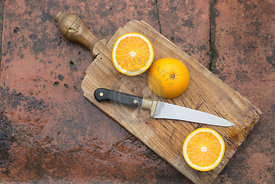 sliced oranges on an old wooden board with cutting knife, against terracotta tile wet surface background