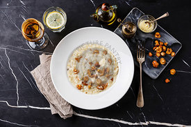 Risotto with chanterelle mushroom on plate on dark marble table background