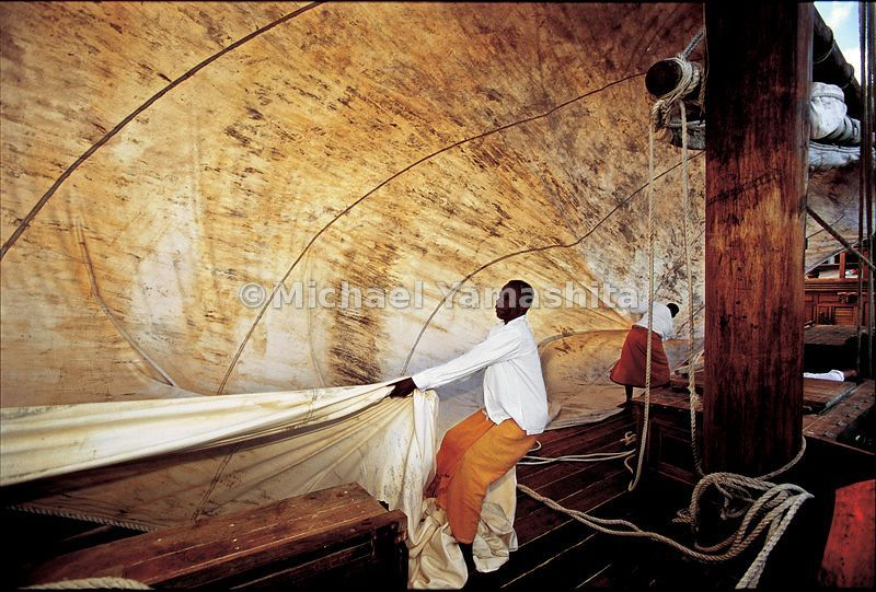 A crewmember grapples with the Sanjeeda's huge sail as the dhow catches the wind.