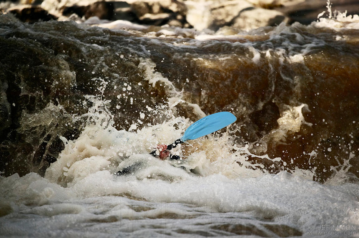 Whitewater kayak submerged by water