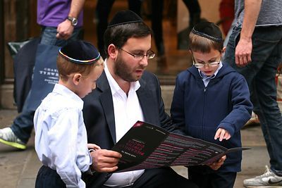 Orthodox Jewish Man reading in the street to his two Small Sons.