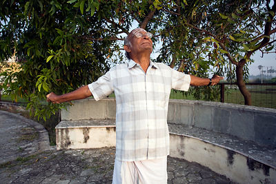 India - Cuddalore - An elderly resident stretches and takes the morning air at dawn by the lake at the Tamaraikulam Elders' Village