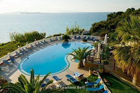 swimming pool of teressa appartments with view across sea, san stefanos, north west corfu, greece.