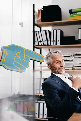 Finger pointing on confident mature businessman in office