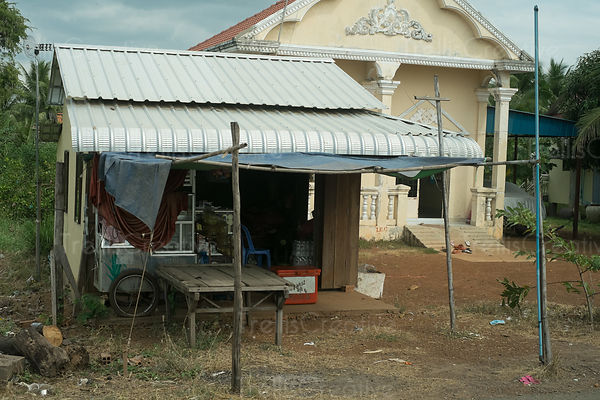 An old road-side shop in Cambodian village next to a fancy home