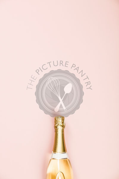 Flat lay of Celebration. Champagne bottle on pink background. Top view, copy space