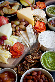 A cheese board of various cheese and crackers.