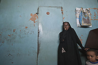 Fatmata Abdulrahman Mbamba, 13, stands in front of an additional division wall in her neighbour's apartment. Adaptations like this, made by the inhabitants, are common in the flats where traditionally large families have had to use the living space to their advantage to accommodate larger extended families.