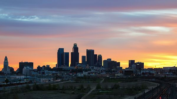 Wide Shot: Traffic, Trains, & a State Park Beset A Fiery Sunset Behind Downtown Los Angeles Skyline (Day To Night)