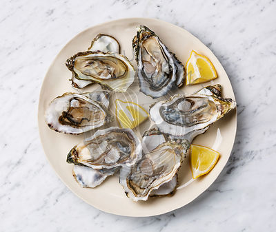 Open shucked Oysters with lemon on white marble background