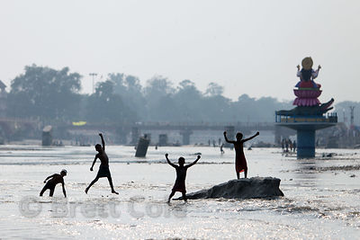 Boys play in the Ganges River near an idol of the river goddess Ma Ganga, Haridwar, India