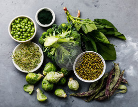 Healthy Green food Clean eating selection Protein source for vegetarians: brussels sprouts, broccoli, spinach, spirulina, green peas on gray concrete background