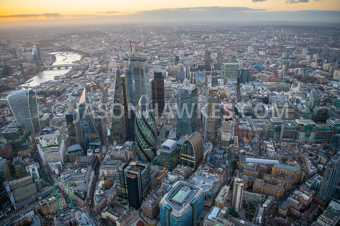 Dusk aerial view of the City of London, London. 17 St Helens Place, 30 St Mary Axe, 100 Bishopsgate, Bevis Marks, Bishopsgate, City of London, Dusk, EC3A 6DG., Heron Tower, Holy Trinity Priory Church, Houndsditch, Liverpool street station, London aerial view, Square Mile, swiss re tower, The Leadenhall Building, The St Botolph Building