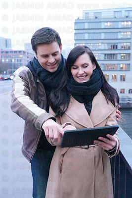 Young couple in the city looking at tablet computer for directions