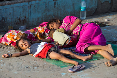A homeless family sleeps on concrete at sunrise near Jama Masjid Mosque, Delhi, India