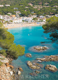 Visitors to the Costa Brava in Spain enjoy the beach and calm water of the bay at Lla franch